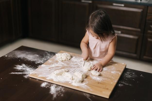 Vista superior da menina cortando massa com uma faca infantil na mesa da cozinha