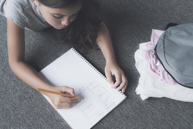 Vista superior da menina desenha no bloco de notas deitado no chão