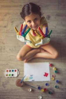 Vista superior da menina encantadora, mostrando as palmas das mãos pintadas