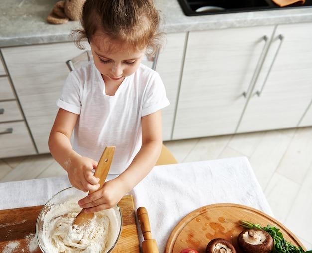 Vista superior da menina fofa focada em amassar a massa. ingredientes da pizza na tábua de madeira. crianças cozinhando