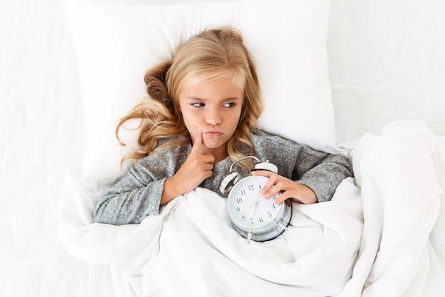 Vista superior da menina pensativa, deitada na cama com o despertador, olhando de lado