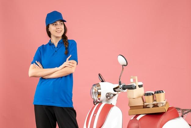 Vista superior da mensageira de entrega em pé perto de uma motocicleta com café e pequenos bolos em um fundo cor de pêssego pastel