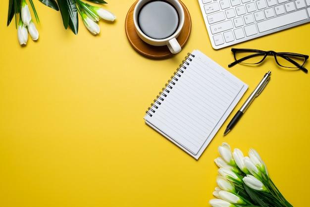 Vista superior da mesa amarela com consumíveis de teclado de flores no espaço da cópia da mesa.