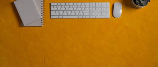 Vista superior da mesa amarela com vaso de planta de notebooks com teclado de computador e espaço de cópia