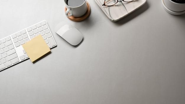 Vista superior da mesa branca com suprimentos de mouse, teclado de computador e espaço de cópia