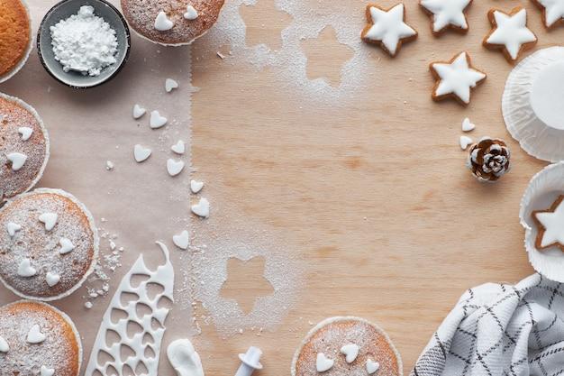 Vista superior da mesa com bolinhos polvilhados de açúcar, cobertura de fondant e cookies de estrelas de natal