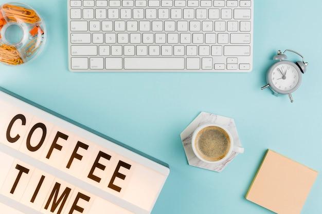 Vista superior da mesa com café e teclado