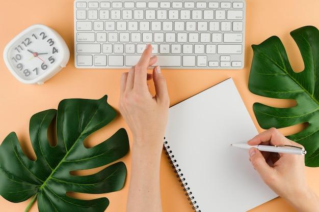 Vista superior da mesa com folhas e teclado
