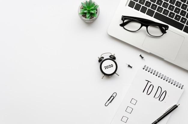 Vista superior da mesa com lista de tarefas e laptop