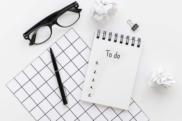 Vista superior da mesa com lista de tarefas e óculos