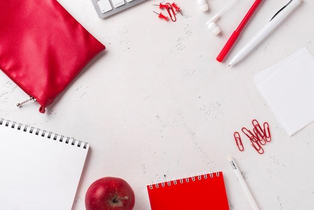 Vista superior da mesa com maçã e artigos de papelaria