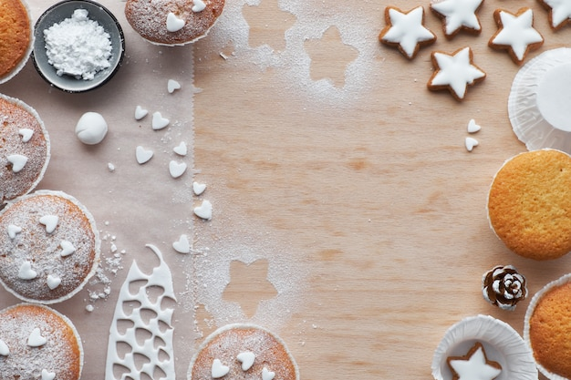 Vista superior da mesa com muffins polvilhados com açúcar, glacê de fondant e biscoitos de estrelas de natal em madeira clara