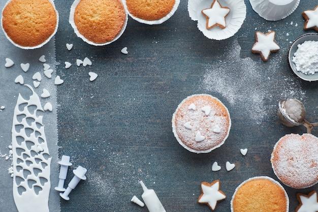Vista superior da mesa com muffins polvilhados de açúcar, glacê de fondant e biscoitos de estrelas de natal em madeira azul