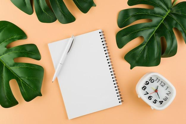 Vista superior da mesa com notebook com folhas e relógio
