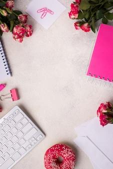 Vista superior da mesa com teclado e buquê de rosas