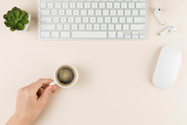 Vista superior da mesa com teclado e mão segurando a xícara de café
