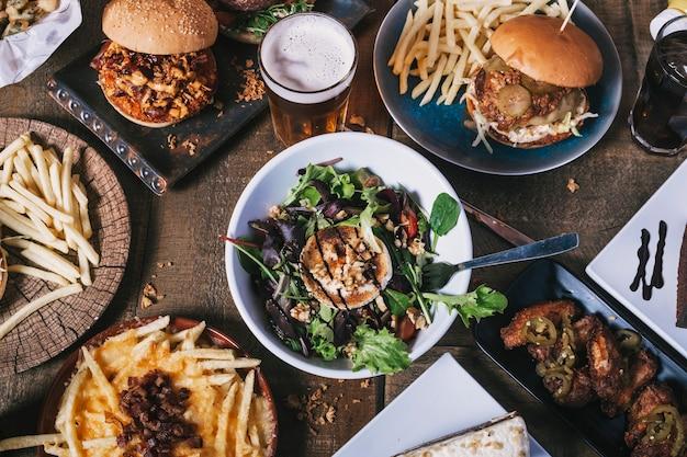Vista superior da mesa com variedade de pratos, hambúrgueres, batatas fritas e salada, bebidas, asas de frango e molho na mesa de madeira. cardápio do restaurante.