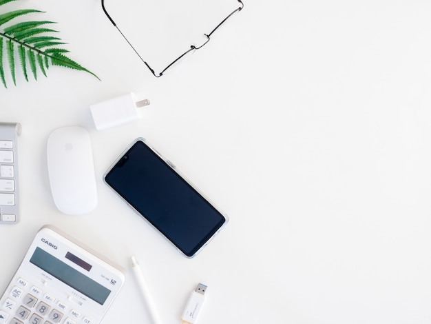 Vista superior da mesa da mesa de escritório com calculadora, caderno, planta plástica, smartphone e teclado em fundo branco, designer gráfico, conceito de designer criativo.