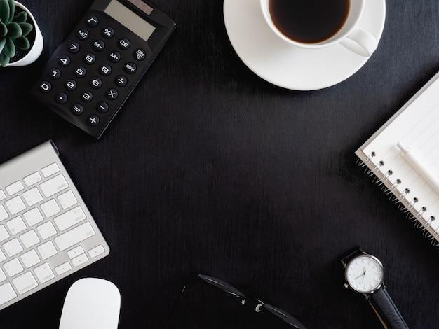 Vista superior da mesa da mesa de escritório com notebook, planta plástica, calculadora e teclado em fundo preto, designer gráfico, conceito creative designer.