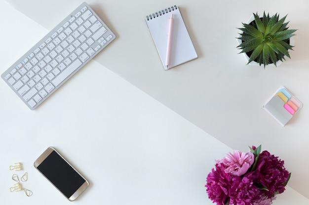 Vista superior da mesa da mesa de escritório ou espaço de trabalho de moda mulher com teclado de computador, diário azul, fundo verde da flor de cacto em pasta. configuração plana