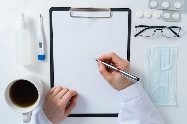 Vista superior da mesa da mesa do médico, papel em branco na área de transferência com caneta. copie o espaço.