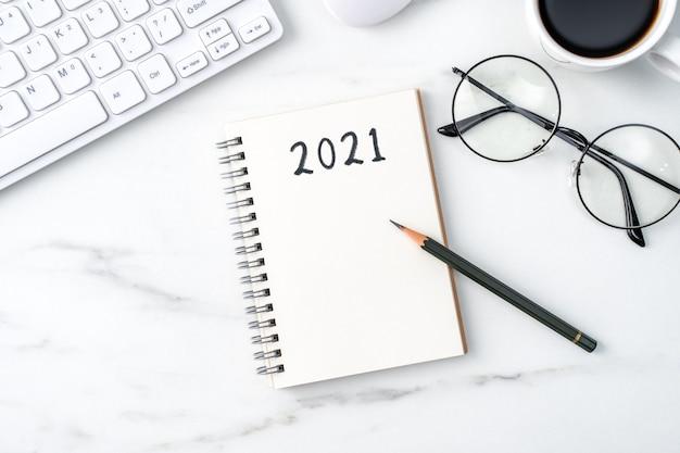 Vista superior da mesa de escritório. 2021 conceito de trabalho de objetivo com teclado, caderno, lápis, óculos e café
