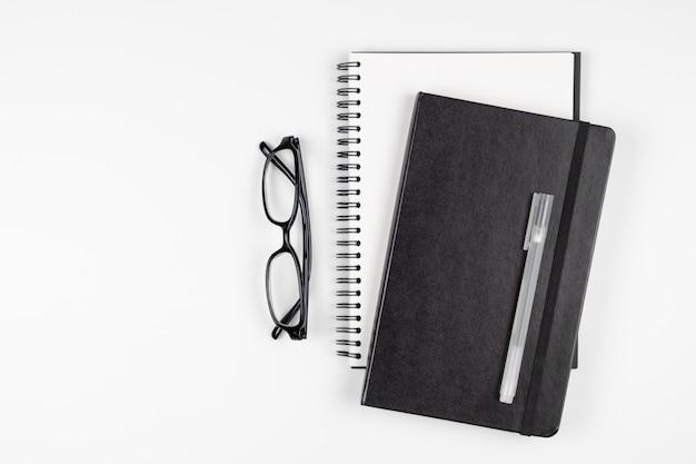 Vista superior da mesa de escritório com caneta e óculos de notebook