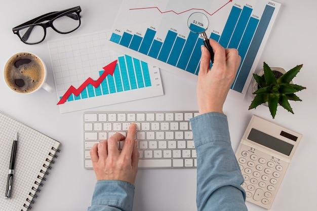 Vista superior da mesa de escritório com gráfico de crescimento e mãos com teclado
