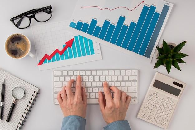 Vista superior da mesa de escritório com gráfico de crescimento e mãos usando o teclado