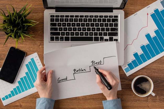 Vista superior da mesa de escritório com gráfico de crescimento nas mãos