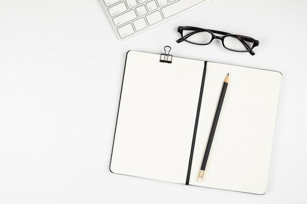 Vista superior da mesa de escritório com lápis e caderno vazio