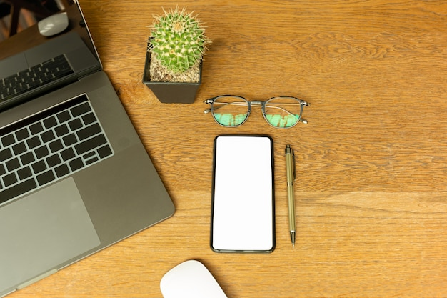 Vista superior da mesa de escritório com laptop, óculos, caneta e computador mouese.
