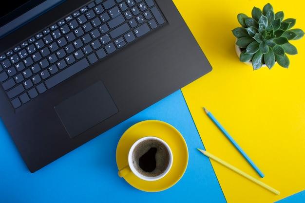 Vista superior da mesa de escritório com laptop, xícara de café, cacto e lápis. postura plana da mesa de trabalho.