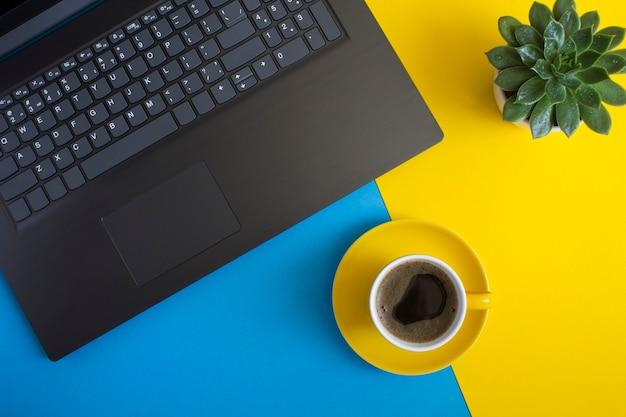 Vista superior da mesa de escritório com laptop, xícara de café e cacto. postura plana da mesa de trabalho.