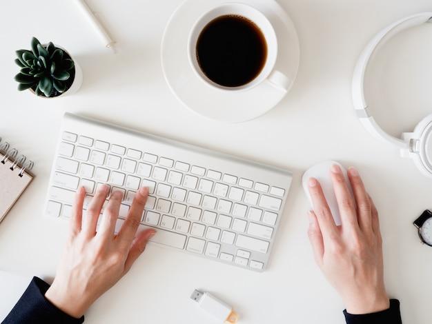 Vista superior da mesa de escritório com mão mulher digitando teclado, notebook, smartphone e gadget no fundo branco