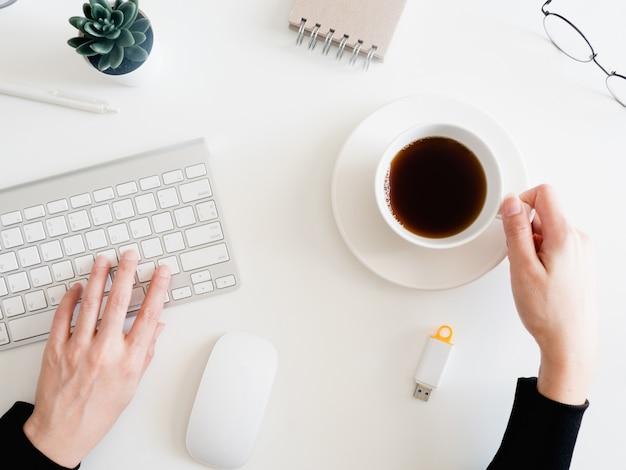 Vista superior da mesa de escritório com mulher mão digitando teclado e segurando a xícara de café