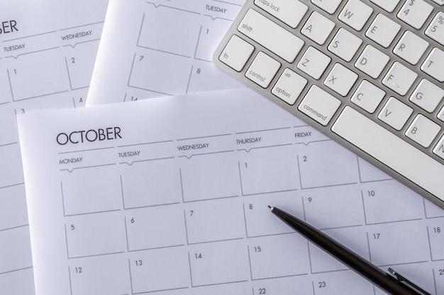 Vista superior da mesa de escritório com teclado e horário de trabalho na mesa branca