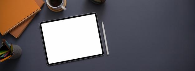 Vista superior da mesa de escritório conceito escuro com tablet mock-up, caneta stylus, material de escritório e xícara de café