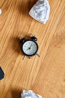 Vista superior da mesa de escritório de madeira com relógio, bolas de papel amassadas, mude sua mentalidade, plano b, hora de definir novas metas, planos,