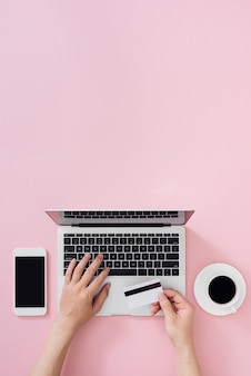 Vista superior da mesa de escritório do empresário com cartão de crédito para pagamento on-line no computador laptop plana sobre cor de fundo