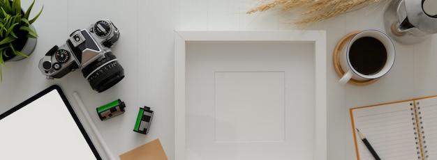 Vista superior da mesa de escritório em casa com moldura de maquete, câmera, xícara de café e decoração