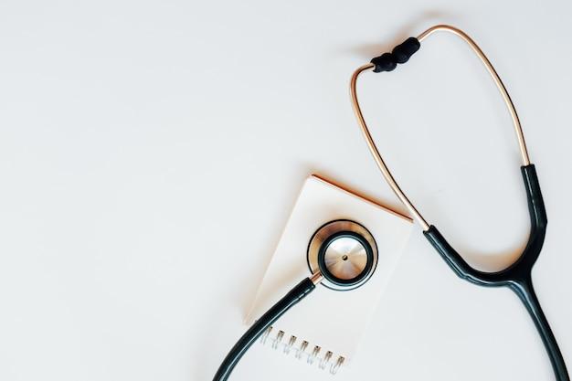 Vista superior da mesa de escritório moderna, estéril dos doutores com o estetoscópio no fundo branco.