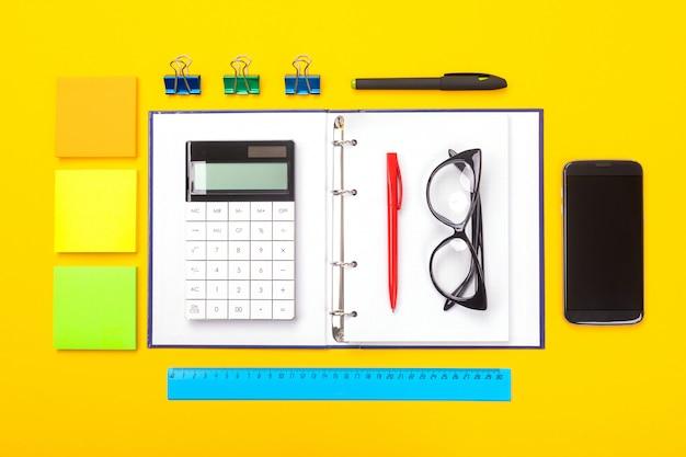 Vista superior da mesa de espaço de trabalho com telefone celular, caderno e caneta