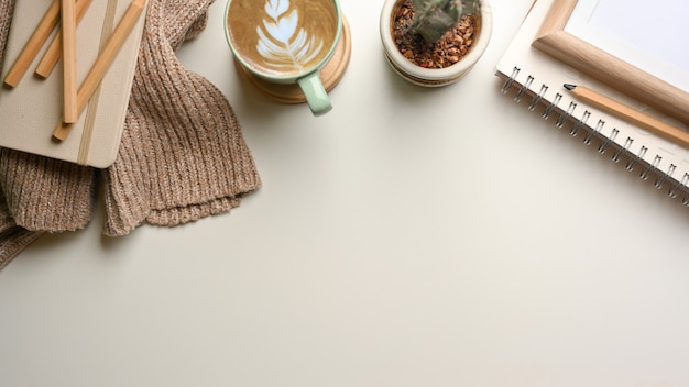 Vista superior da mesa de estudo simples com livros de papelaria de suéter xícara de café, pote de cacto e espaço de cópia