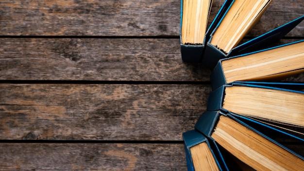 Vista superior da mesa de madeira com livros e espaço de cópia