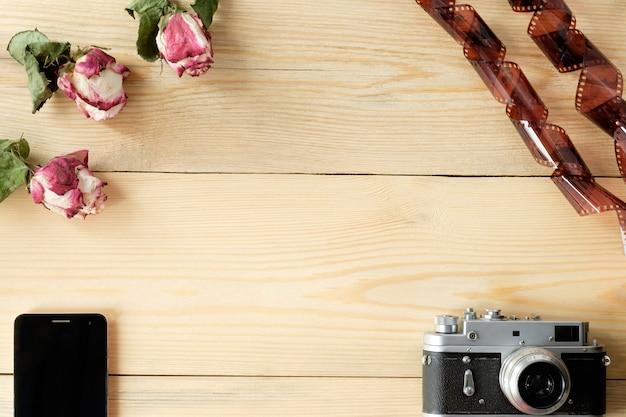Vista superior da mesa de madeira com smartphone, câmera vintage, filme e rosas secas com folhas