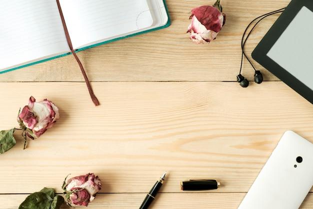 Vista superior da mesa de madeira com smartphone, fones de ouvido, e-book; caneta, diário e rosas secas e folhas