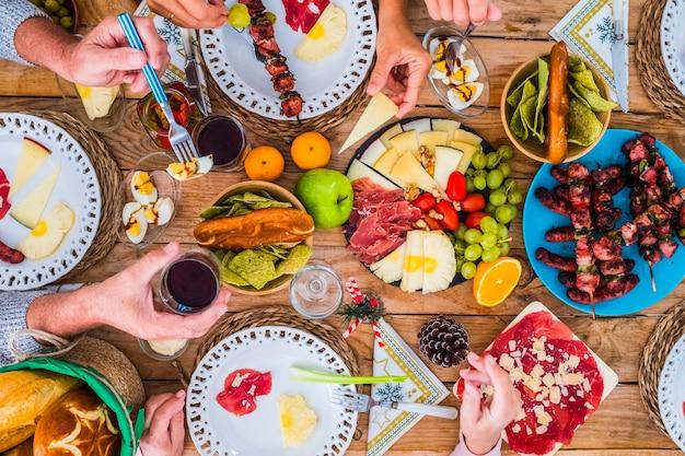 Vista superior da mesa de madeira da celebração do natal cheia de decorações de comida e pessoas se divertindo juntas