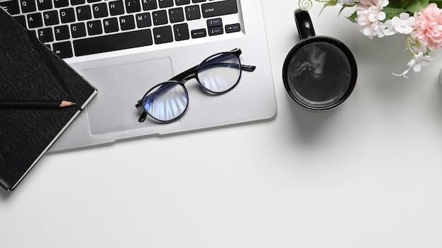 Vista superior da mesa de mesa de escritório branca com notebook, laptop, xícara de café, copos e espaço de cópia.