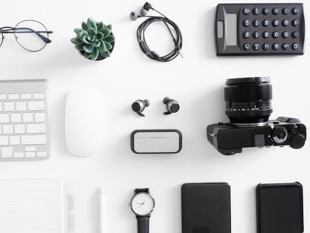 Vista superior da mesa de mesa de escritório com calculadora, notebook, planta plástica, smartphone e teclado em branco